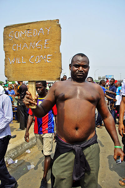 "A man poses with a poster which says ""One day change will come"""