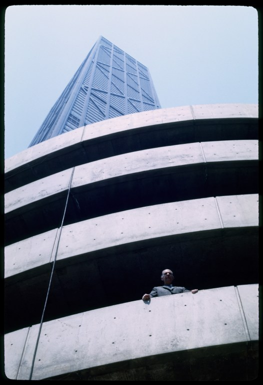 Man standing on an outdoor balcony of a building, looking out of the picture toward the viewer, with a skyscraper rising above him.