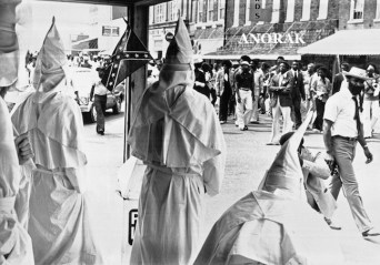 Robed Ku Klux Klansmen watch from sidewalk, as black demonstrators march through Okolona, Miss., Saturday, August 26, 1978, to demand increased minority hiring. There were no major incidents reported between the 36 Klansmen and some 300 black demonstrators. The marchers said they intend to continue a boycott of area stores, which has been in progress over the past week. (AP Photo/JM)