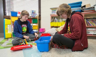 two students play with toys in Alex's class