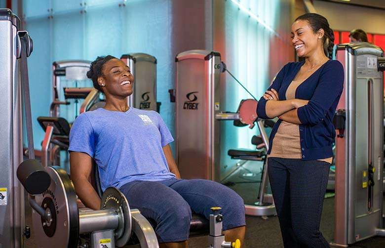 Dr. Perkins talks with a student working out on a resistance machine inside Foster Recreation Center