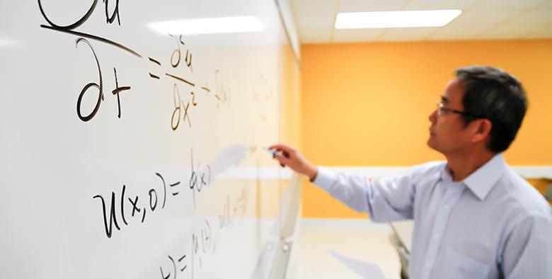 Dr. Hu writing an equation on a whiteboard
