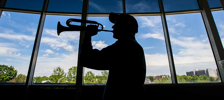 Dr. John Prescott playing trumpet in silhouette
