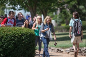 Students walking on campus while looking at smartphones