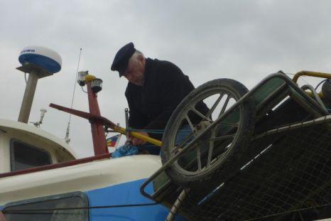 Axel Rohwedder zurrt die Karren auf dem Boot fest (Foto: Tore J. Mayland-Quellhorst).