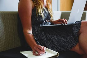 Girl writing in notebook while on computer