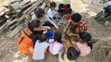 Peeling cashew nuts with members in the commune.