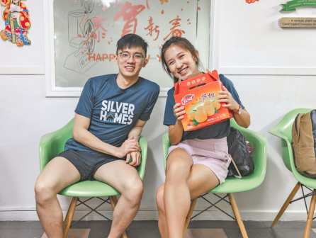 Volunteers giving out mandarin oranges to the elderly.