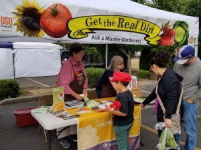 Two Master Gardeners standing under a canopy with a banner reading 'Get the Real Dirt Ask a Master Gardener', talking to a man, woman, and child.