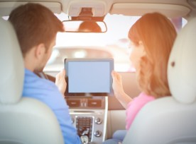 Couple driving with tablet computer