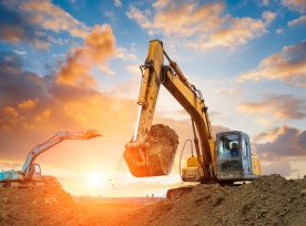 Excavator In Construction Site On Sunset Sky
