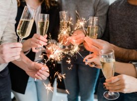 Group Of Friends Holding Flutes Of Sparkling Champagne And Burning Bengal Lights