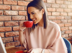 Portrait Of Attractive Young Caucasian Woman With Brown Hair And Toothy Smile Drinking Coffee While Sitting In Cafeteria And Looking At Laptop.
