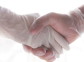 Coronavirus Two People Shaking Hands With Gloves To Avoid Contagion