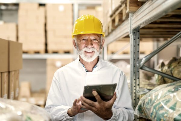 Smiling Senior Worker In Uniform And With Yellow Helmet On Head Holding Tablet And Looking At Camera While Standing In Storage.