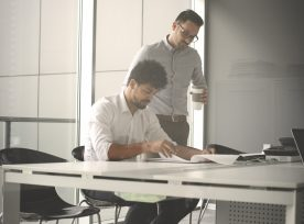 Two Business Men Working Together In Office. Reading Document.