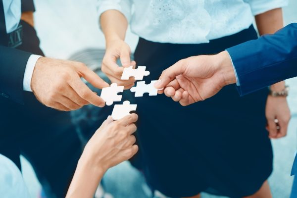 Close,up,at,a,businessman,holding,hands.,four,puzzles,come