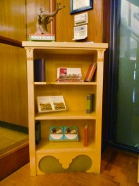 The accompanying books are made of wood, with a few displaying comical spine titles.