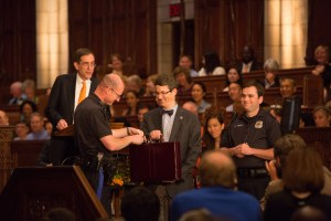 In his Class Day speech, Eisgruber (back at the lectern) joked that the real reason the senior class invited Nolan to speak was to settle the debate about whether Batman went to Princeton or Yale. Eisgruber asked University Archivist Dan Linke (center with briefcase) to help answer the question by presenting Batman's secret alumni records. Photo: Princeton University, Office of Communications, John Jameson (2015)