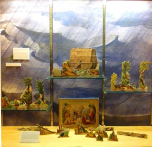 Full set of l'arche de Noé: the ark, stand-up figures and scenery, and illustrated box, with Hutton's artwork as background.