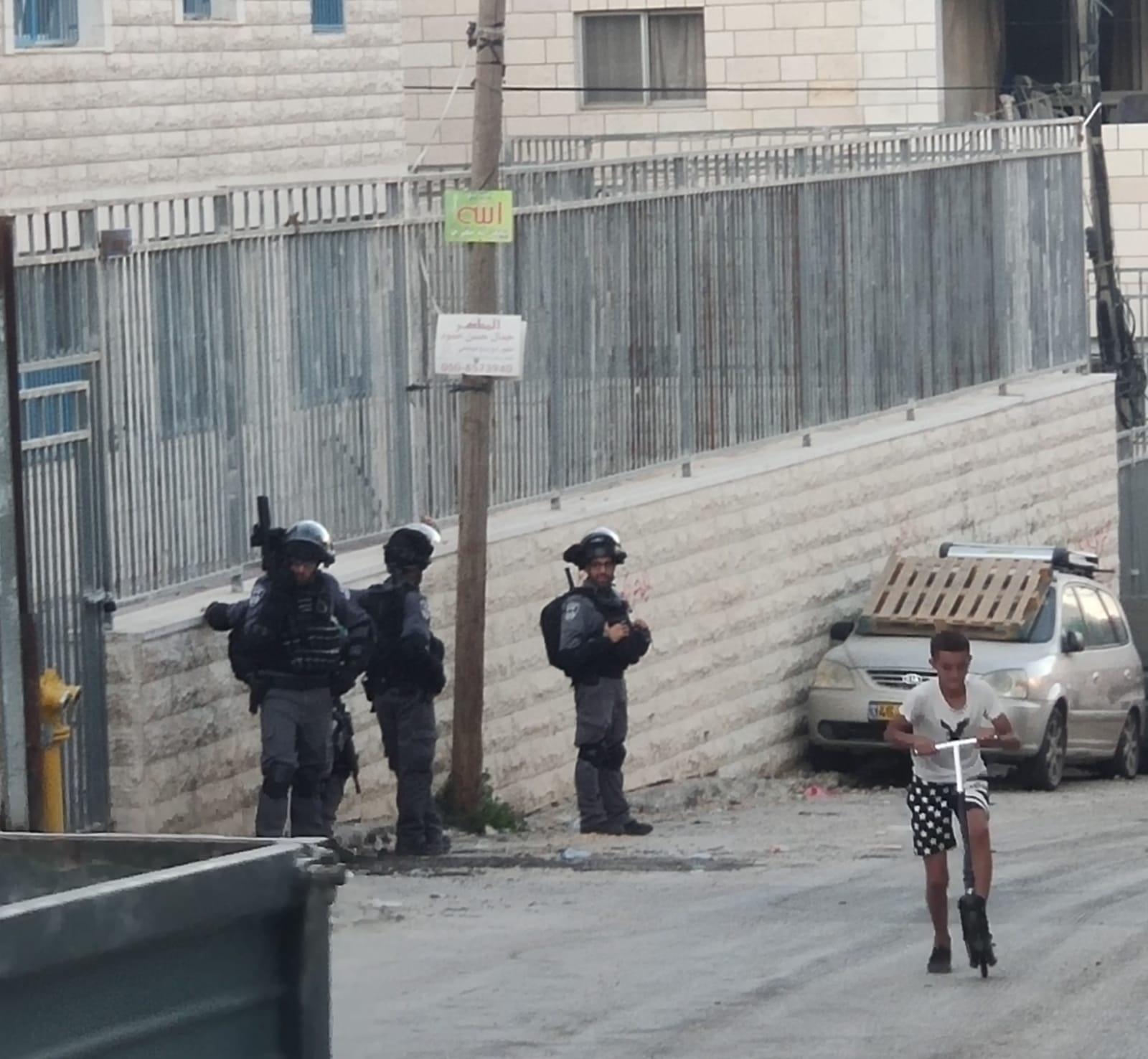 Un niño juega con su patinete en frente de una patrulla de soldados Israelíes