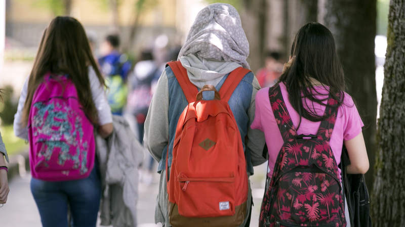 Tres escolares, una de ellas vistiendo velo, a la salida del colegio en Vitoria. EFE/David Aguilar