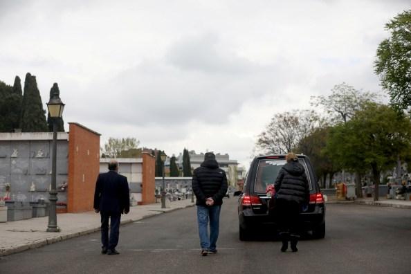 Familiares siguen el coche fúnebre con los restos de uno de los fallecidos por el coronavirus, en un cementerio de Madrid. REUTERS/Susana Vera