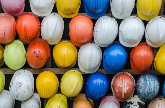 Multi-coloured hard hats in rows