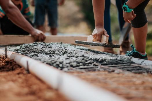 Image: volunteers leveling concrete