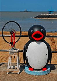 An image of a penguin statue by the seaside