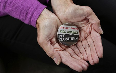 An image of a badge held in a pair of hands. The badge reads 'It's our future / Kids against pit closures'