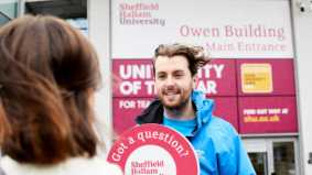 Student ambassador outside Sheffield Hallam University's main reception, welcoming a prospective student to an open day.