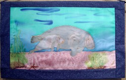 Handpainted silk wall hanging with an endangered manatee design by Judy Elliott