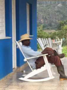 image of Cuban man sitting on a rocking chair on a porch by Judy Morris