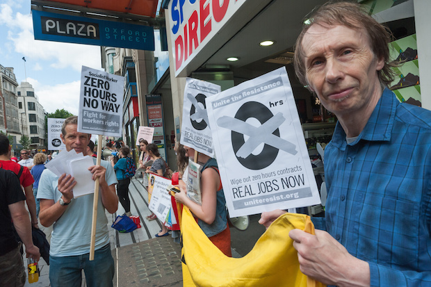 London, United Kingdom. 3rd August 2013 -- People hold placards in Oxford St London protest against use of zero-hours contracts for more than 85 percent of Sports Direct workforce.