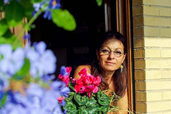 Older woman facing camera behind flowers