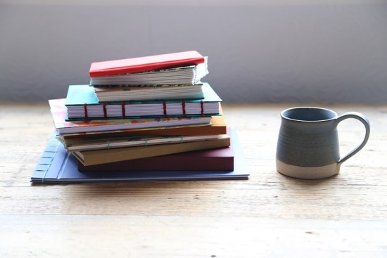 Pile of bound notebooks with small mug