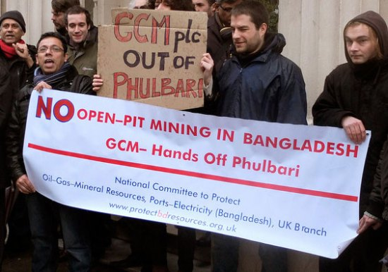 Protestors standing with a banner saying no open-pit mining in Bangladesh.