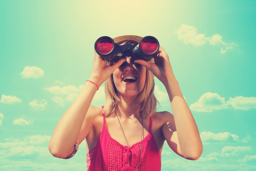 Woman looking excitedly through a pair of binoculars.