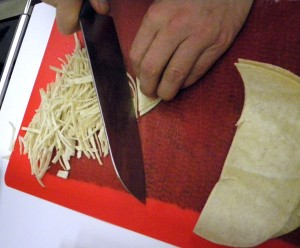 slicing tortillas into fine strips for the sopa Tarasca