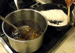 boiling the dried chiles until soft, and, in the background, frying the rice until it turns golden and sounds like 'sand in the pan'
