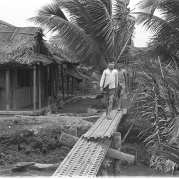 Black-and-white photo of two children walking across a footbridge