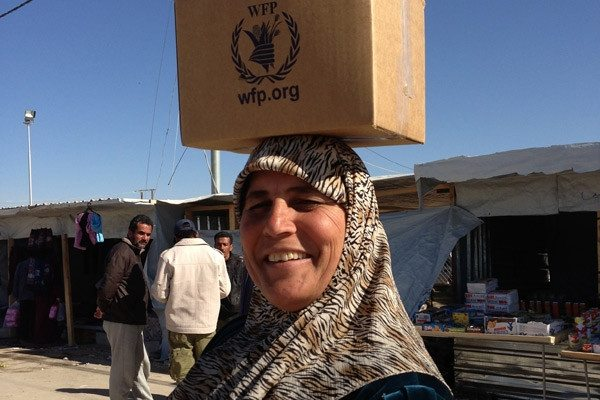 A Syrian refugee smiles as she carries WFP food home to her family.  Thanks to WFP for posting this photo and more on their Twitter page.