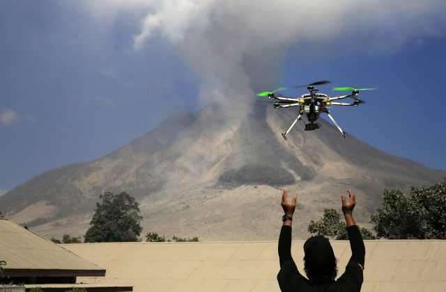 An official of the Center for Research and Technology Volcanoes Development (BPPTK) releases a drone quadcopter to monitor activity from the Mount Sinabung volcano in Sumatra, Indonesia (Reuters)