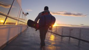 Still of an HDR video showing a man with a a snowboard and a backpack walking toward a sunset