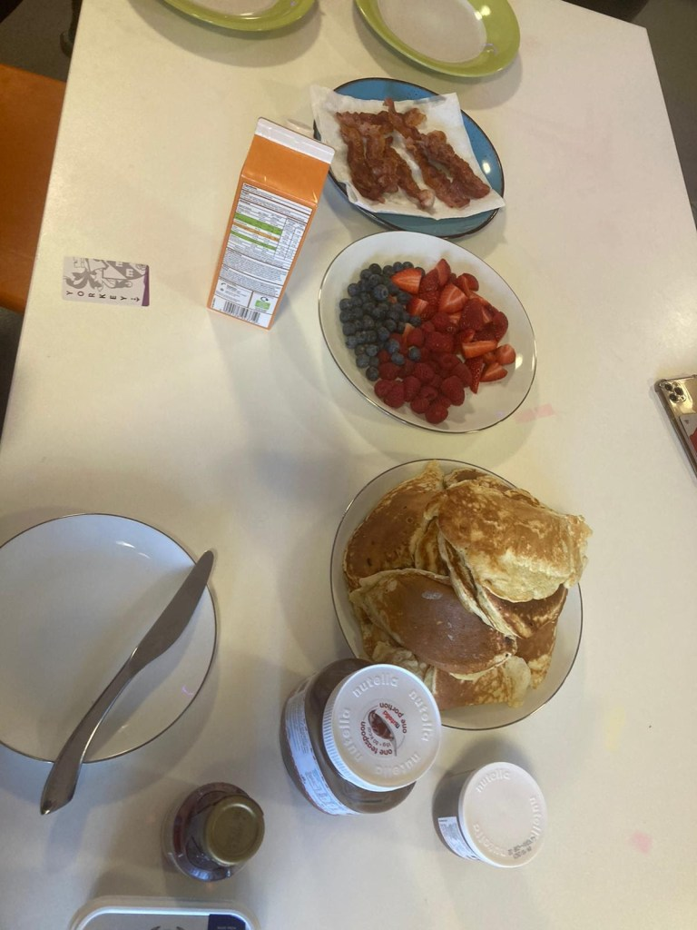 Anais' American style pancakes on the kitchen table. Served with bacon, berries, orange juice, Nutella and syrup.