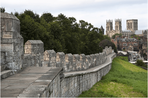 Image of the city walls in York city centre, York Minster and Lendal Bridge are visible in the background