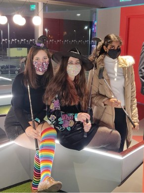 Three female students dressed in halloween costumes with golf clubs at a minigolf course