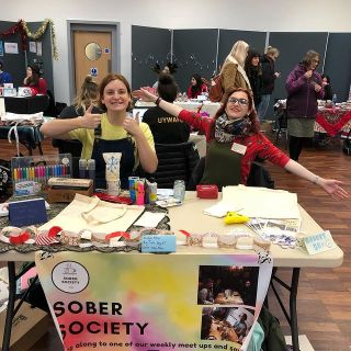 Two people sit at a white table covered in craft supplies, both are smiling. There is a colourful banner on the front of the table with 'Sober Society' written on it. In the background are other stalls and people walking around looking at them.