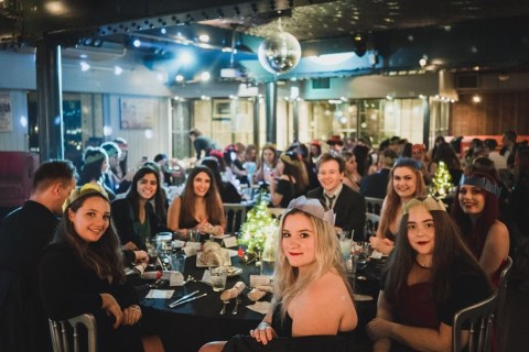 A group of students sitting around a large table at an evening event. There's a glitter ball hanging from the ceiling.